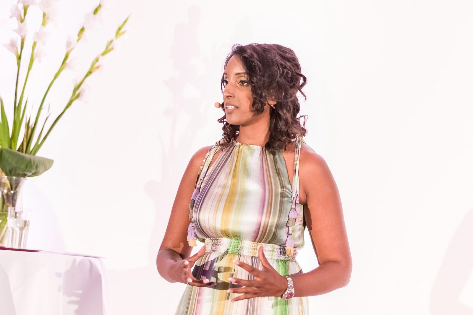 Bild zeigt Sabina Kocherhans im gestreiften Kleid während ihrer Keynote auf der Veranstaltung des Feminss-Kongress 2018