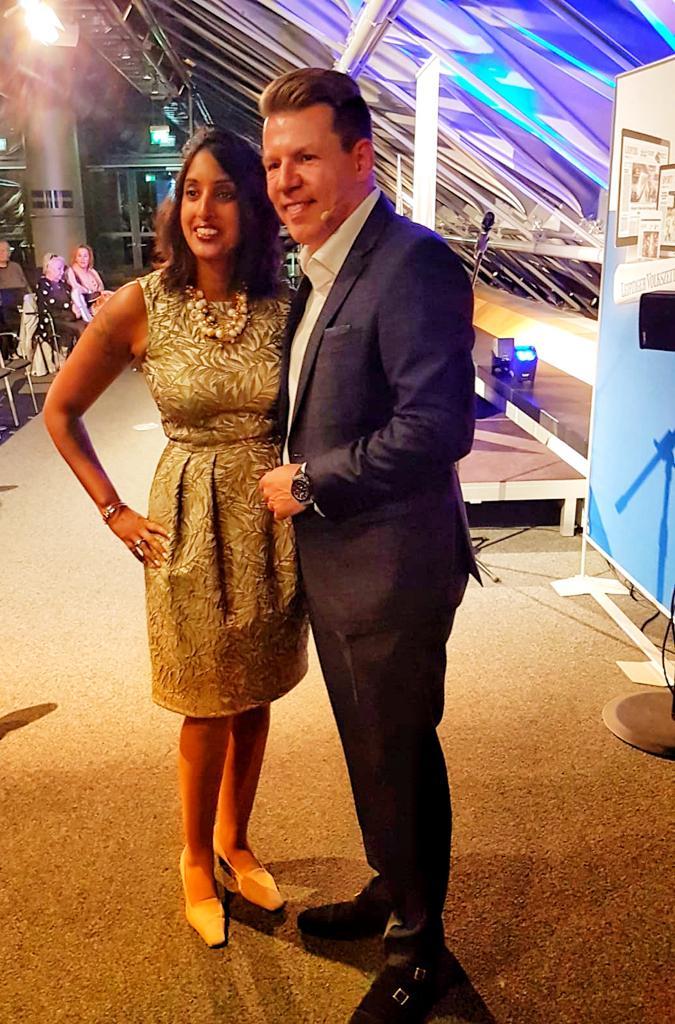 Bild zeigt Sabina Kocherhans im goldfarbenen Kleid stehend neben Axel Kahn auf seiner Veranstaltung