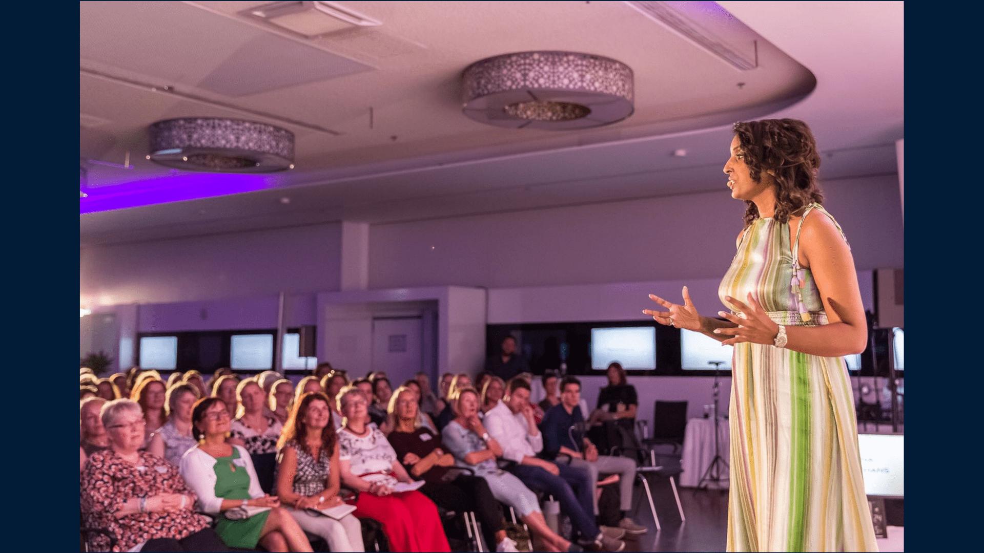 Bild zeigt Sabina Kocherhans in längs bunt gestreiftem langen Kleid auf der Bühne während ihrer Keynote beim Feminss-Kongress 2018