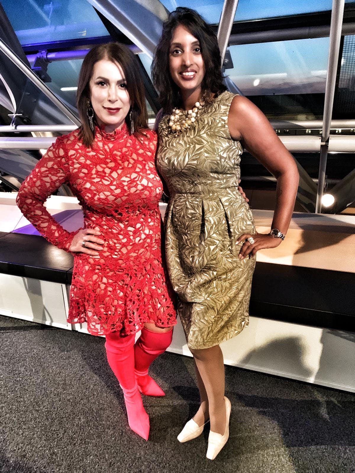 Bild zeigt Sabina Kocherhans im goldfarbenen Kleid mit einer Veranstaltungs-Teilnehmerin in einem roten Häkel-Kleid nebeneinander stehend