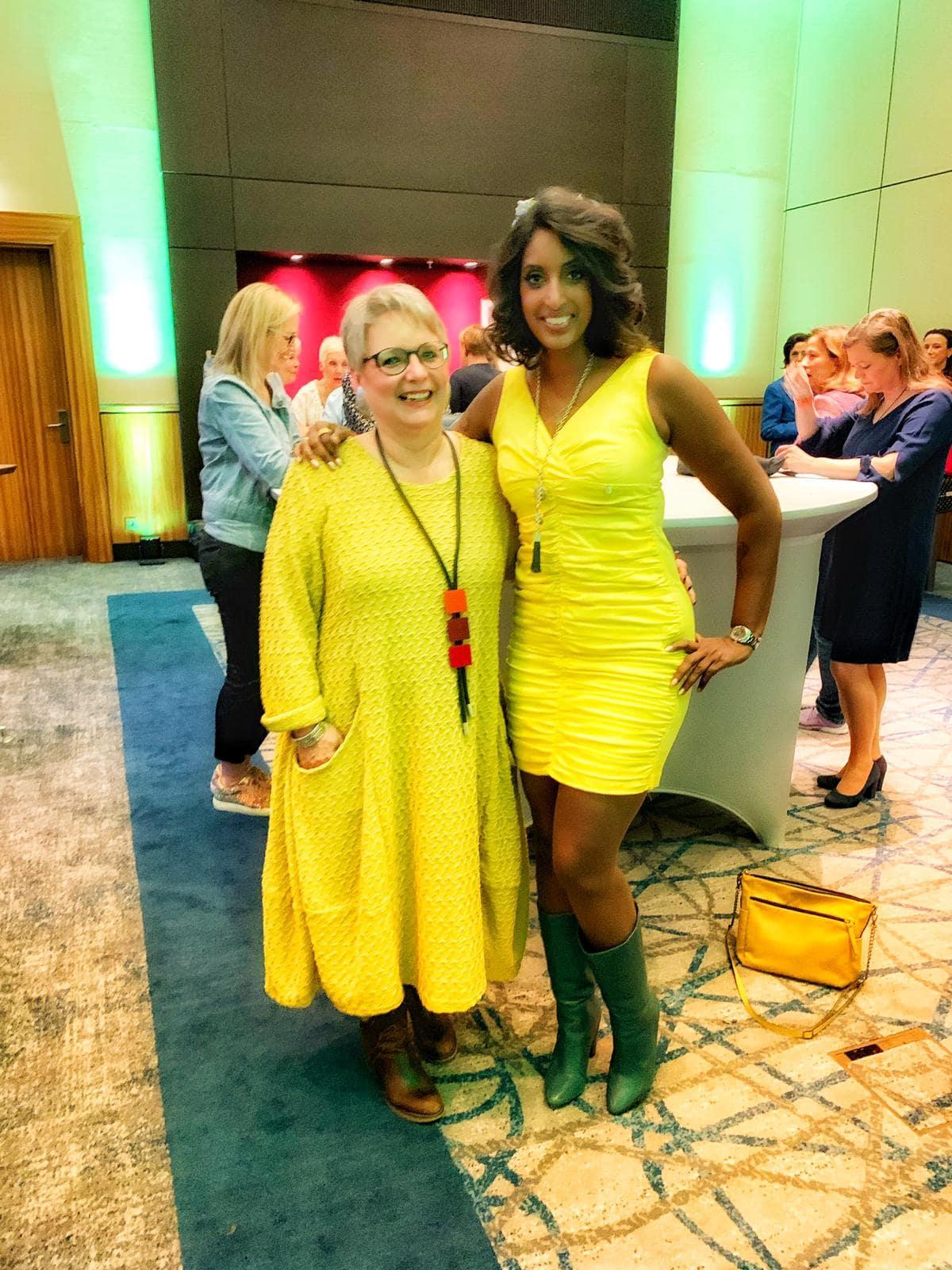 Bild zeigt eine Veranstaltungsteilnehmerin und Sabina Kocherhans im Gespräch - beide im gelben Kleid